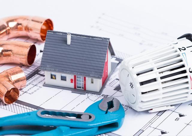Makieta domu obok głowicy termostatycznej naprojekcie budowlanym