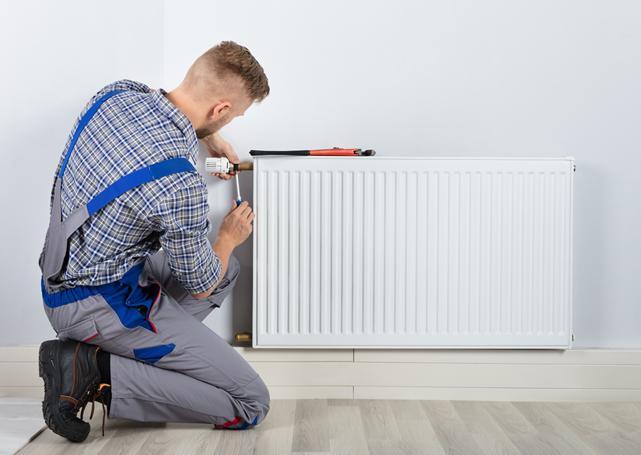 Pracownik montuje głowicę termostatyczną dogrzejnika